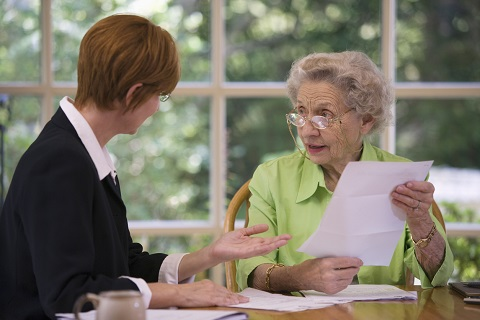 Elderly woman consulting a Wisconsin real estate lawyer to transfer property
